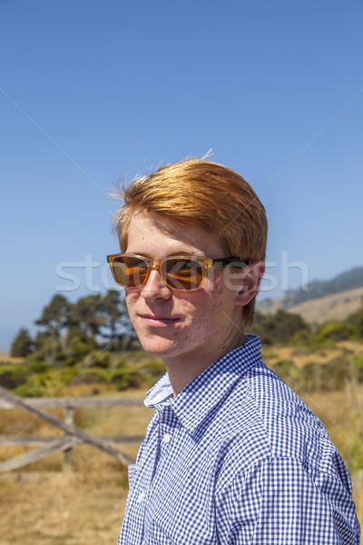 cool teenage boy with sunglasses walks happy on the meadow Stock photo © meinzahn
