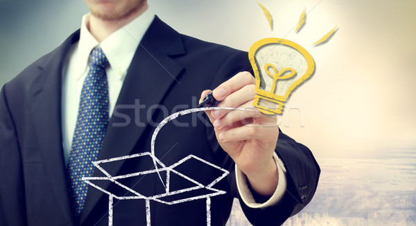 Stock photo: Business man with idea light bulb coming 'out of the box'