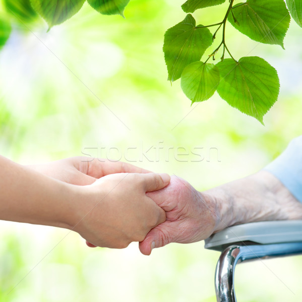 Senior woman in wheel chair holding hands with young caretaker Stock photo © Melpomene