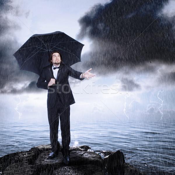 Man Under Umbrella Checking for Rain Coming or Clearing Stock photo © Melpomene