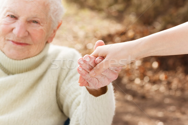 Senior woman holding hands with young lady Stock photo © Melpomene