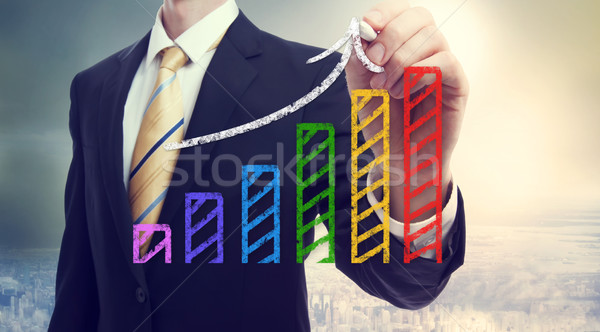 Businessman drawing a rising arrow over a bar graph Stock photo © Melpomene