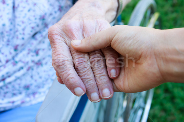 Caregiver holding seniors hand Stock photo © Melpomene