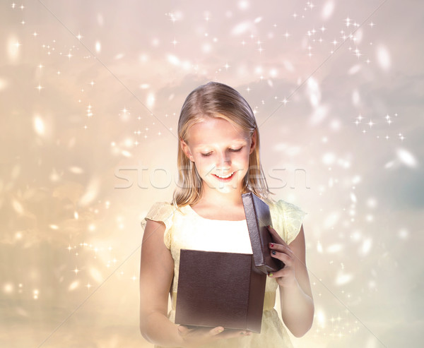 Happy Blond Girl Opening a Present Stock photo © Melpomene