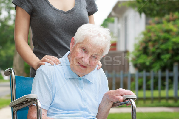Happy senior lady in wheelchair with caregiver Stock photo © Melpomene