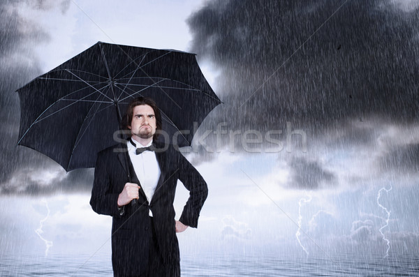 Man Holding Umbrella in the Rain and Frowning  Stock photo © Melpomene