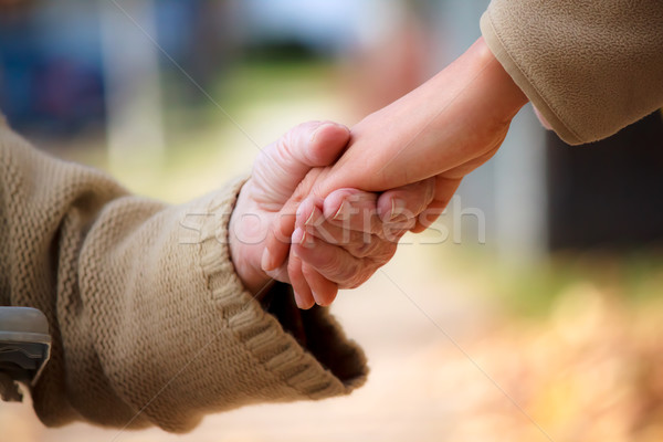 Senior and young holding hands Stock photo © Melpomene