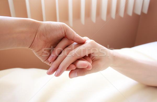 Holding hand of a sick loved one Stock photo © Melpomene