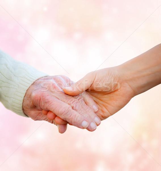 Supérieurs dame mains tenant jeune femme rose lumières Photo stock © Melpomene