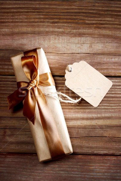 Gift box on a rustic wooden table with a blank tag Stock photo © Melpomene