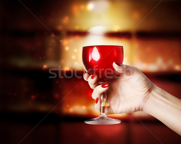 Wine glass being held in a womans hand Stock photo © Melpomene