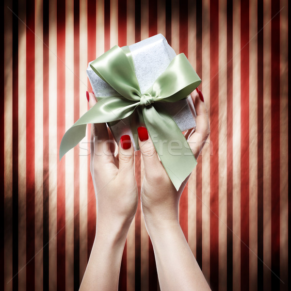 Hand with red nails holding a gift box Stock photo © Melpomene