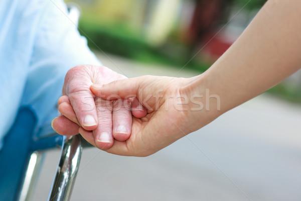 Senior women in wheelchair holding hands Stock photo © Melpomene