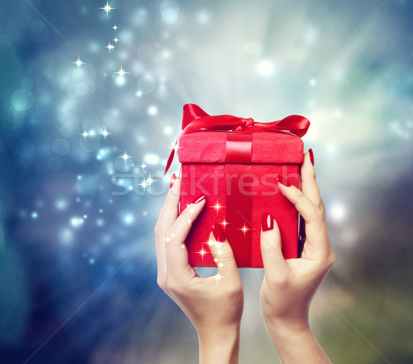 Red present box held up by in a woman's hands Stock photo © Melpomene