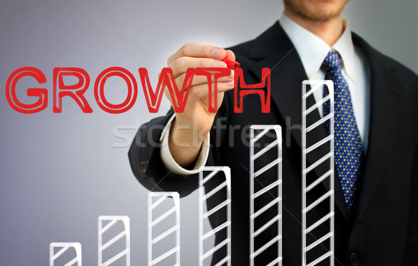 Businessman writing growth over a bar graph Stock photo © Melpomene