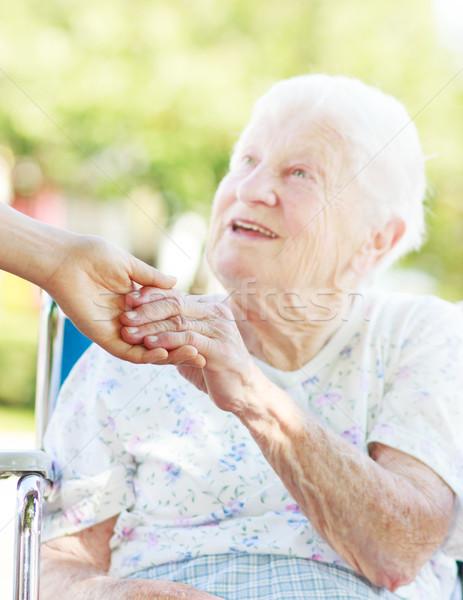 Senior vrouw holding handen rolstoel buiten familie Stockfoto © Melpomene