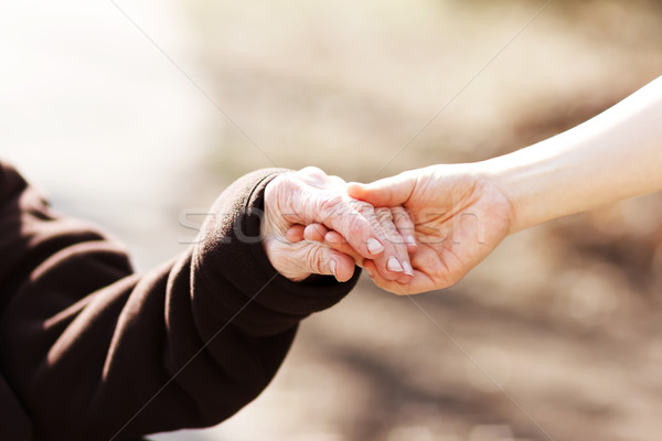 Senior woman holding hands with young caretaker Stock photo © Melpomene