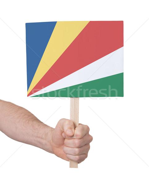 Kéz tart kicsi kártya zászló Seychelle-szigetek Stock fotó © michaklootwijk