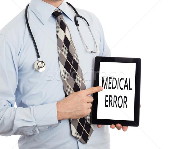 Doctor holding tablet - Medical error Stock photo © michaklootwijk