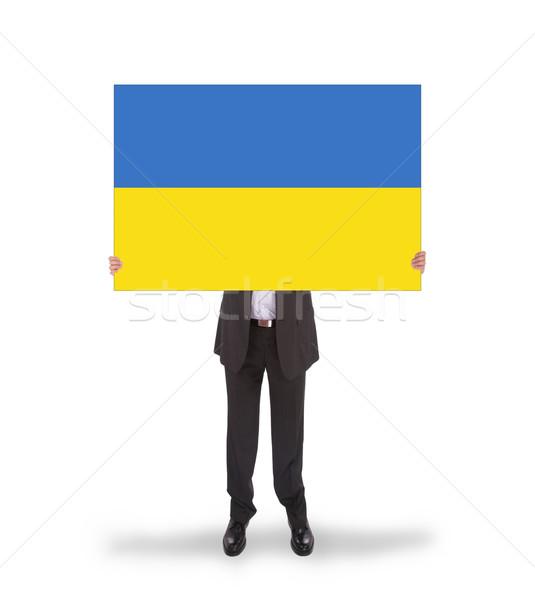 Smiling businessman holding a big card, flag of Ukraine Stock photo © michaklootwijk