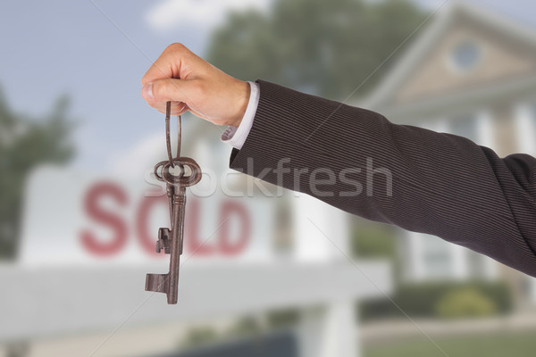 Stock photo: Man in suit giving old keys