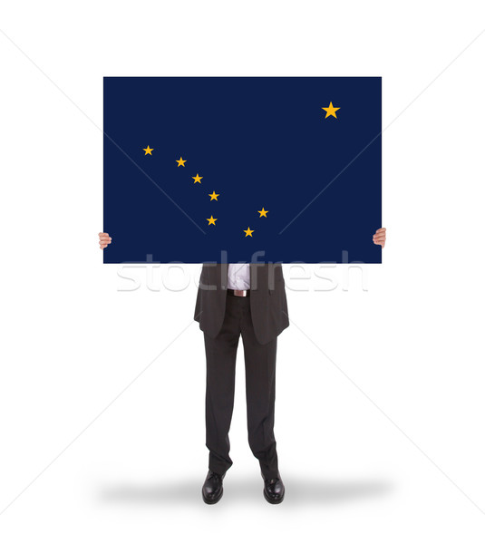 Smiling businessman holding a big card, flag of Alaska Stock photo © michaklootwijk