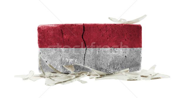 Baksteen gebroken glas geweld vlag Indonesië muur Stockfoto © michaklootwijk