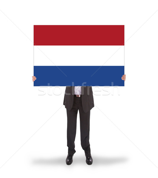 Smiling businessman holding a big card, flag of the Netherlands Stock photo © michaklootwijk