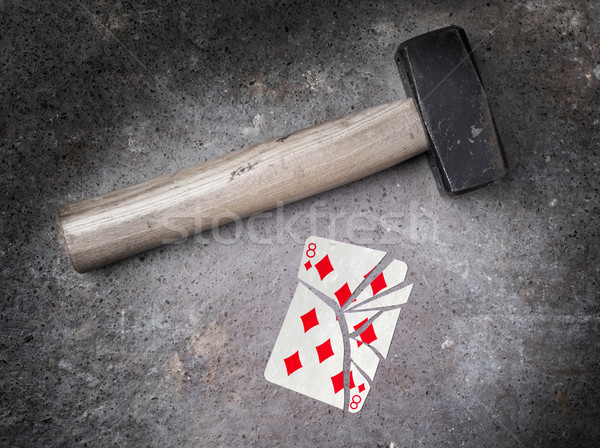 Stock photo: Hammer with a broken card, eight of diamonds
