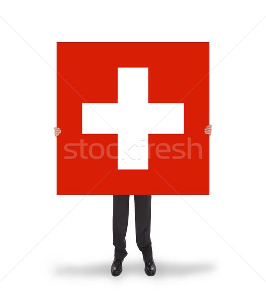 Smiling businessman holding a big card, flag of Switzerland Stock photo © michaklootwijk