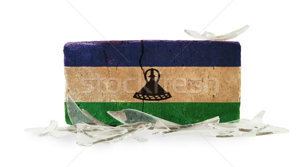 Baksteen gebroken glas geweld vlag Lesotho muur Stockfoto © michaklootwijk