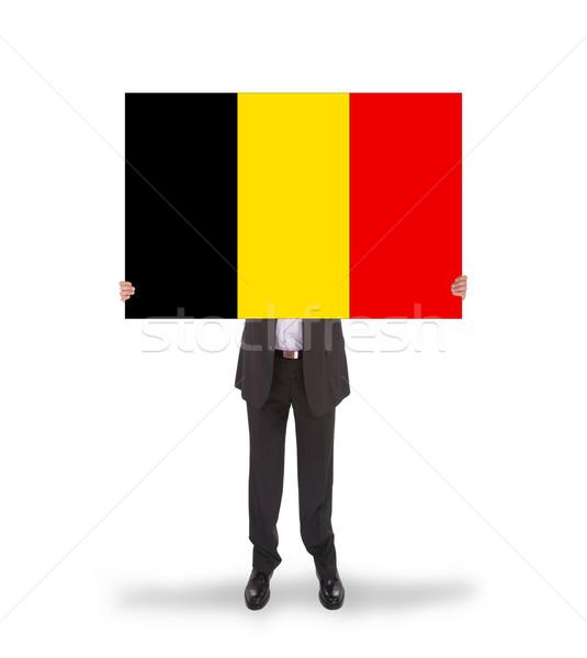Smiling businessman holding a big card, flag of Belgium Stock photo © michaklootwijk