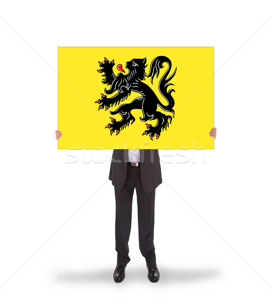 Smiling businessman holding a big card, flag of Flanders Stock photo © michaklootwijk
