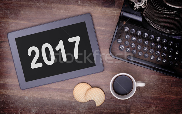 Tablet touch computer gadget on wooden table - 2017 Stock photo © michaklootwijk