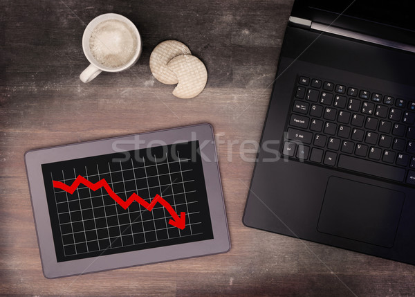 Tablet touch computer gadget on wooden table, graph negative Stock photo © michaklootwijk
