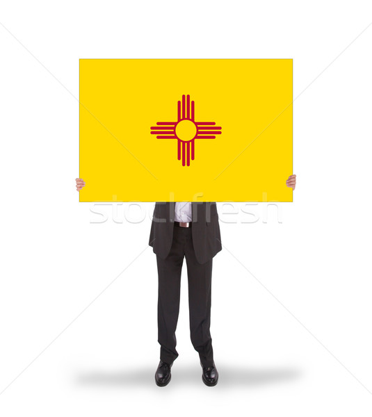 Smiling businessman holding a big card, flag of New Mexico Stock photo © michaklootwijk
