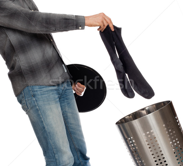 Young man putting dirty socks in a laundry basket Stock photo © michaklootwijk