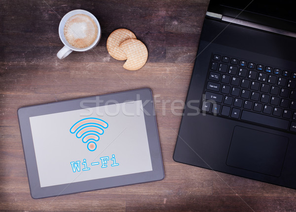 Tablet with Wi-Fi connection on a wooden desk Stock photo © michaklootwijk