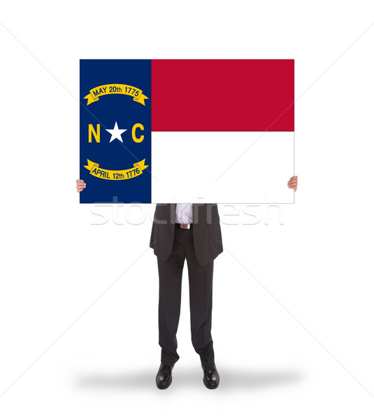 Smiling businessman holding a big card, flag of North Carolina Stock photo © michaklootwijk