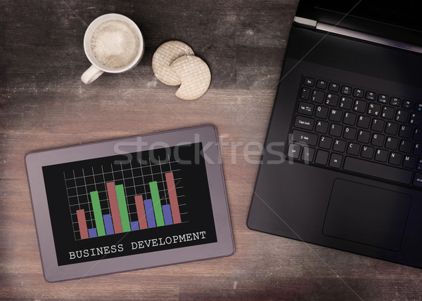 Tablet touch computer gadget on wooden table, graph Stock photo © michaklootwijk