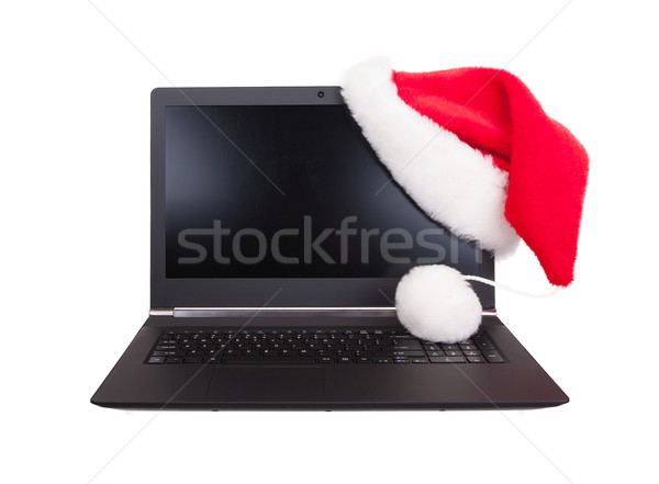 Modern open laptop with red santa claus hat put on lcd corner Stock photo © michaklootwijk