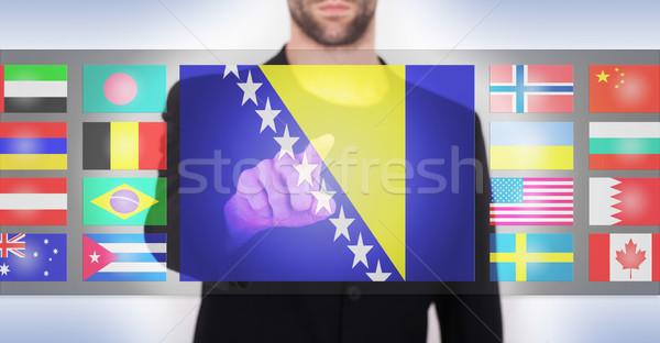 Mano empujando pantalla táctil interfaz idioma Foto stock © michaklootwijk