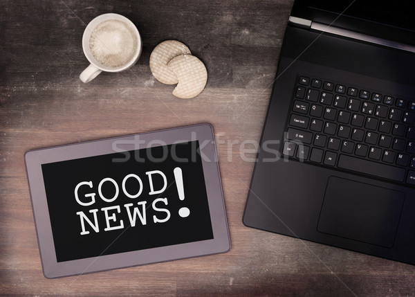Tablet touch computer gadget on wooden table, good news Stock photo © michaklootwijk