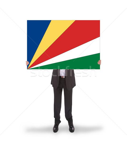Businessman holding a big card, flag of Seychelles Stock photo © michaklootwijk