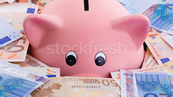 Unique pink ceramic piggy bank drowning in money Stock photo © michaklootwijk
