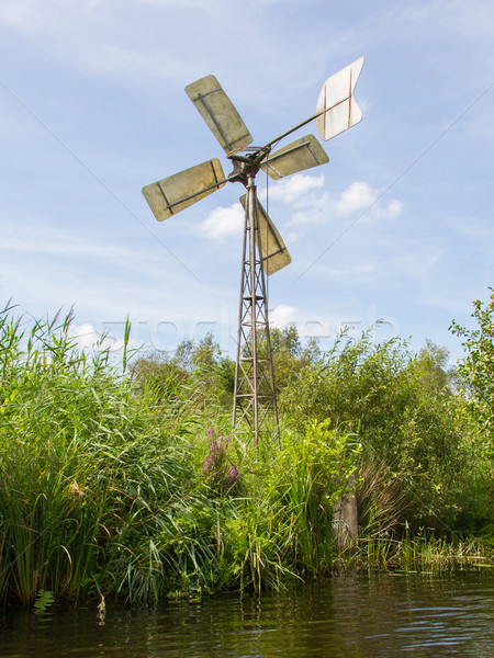 Small and rusted old metal windmill at the waterside Stock photo © michaklootwijk