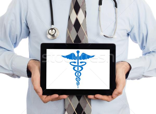 Doctor holding tablet - Caduceus symbol Stock photo © michaklootwijk
