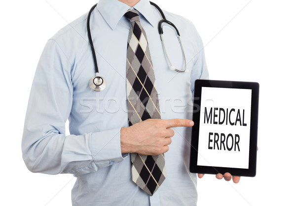 Doctor holding tablet - Medical error Stock photo © michaklootwijk