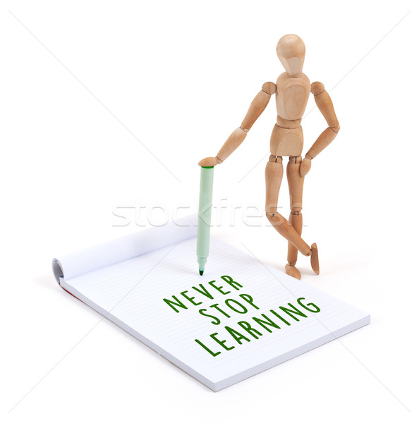 Wooden mannequin writing in scrapbook - Never stop learning Stock photo © michaklootwijk