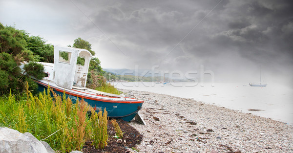 Small shipwreck at a loch with stone beach Stock photo © michaklootwijk